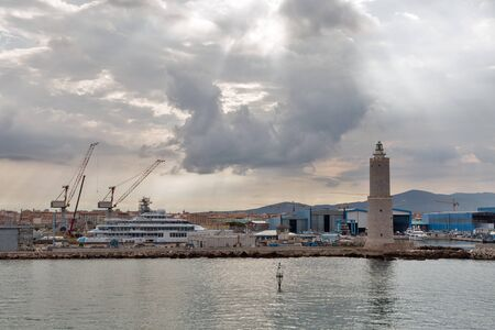 Cityscape with lighthouse and Livorno port at dramatic sky dawn. The Port of Livorno is one of the largest seaports both in Italy and the Mediterranean Sea.