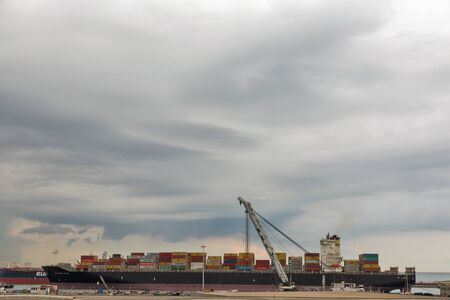 LIVORNO, ITALY - JULY 12, 2019: Cargo ship with containers in Livorno port terminal at dawn. Livorno is a port city on the Ligurian Sea on the western coast of Tuscany. Archivio Fotografico - 133522542