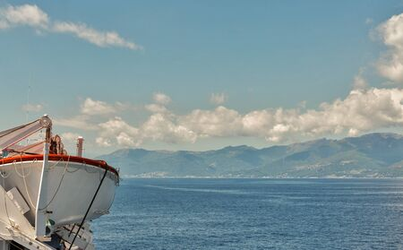 Cruise ship deck with lifeboat against cloudy sky background. Ligurian sea, Italy.