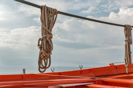 Hanging ship ropes and red lifeboat closeup against seascape and cloudy sky 版權商用圖片