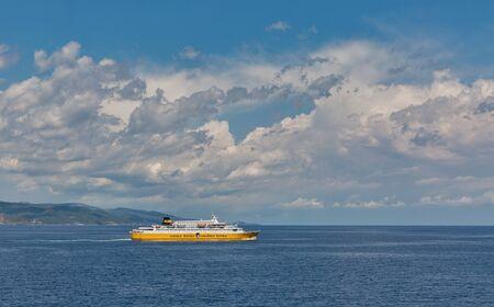 CORSICA, FRANCE - JULY 12, 2019: Corsica Ferries - Sardinia Ferries ship sailing in the sea with dramatic clouds. It is a ferry company that operates traffic to and from Corsica, Sardinia and Elba.