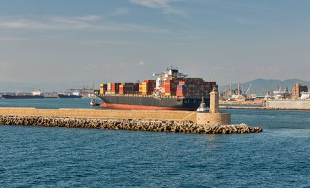 Tugs and huge cargo container ship entering port of Livorno, Tuscany, Italy.
