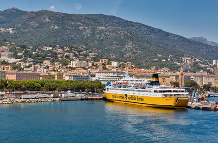 BASTIA, CORSICA, FRANCE - JULY 23, 2019: Cityscape with passenger port and moored Corsica Viktoria ferry ship by Corsica Ferries Sardinia Ferries. Bastia port is the busiest French Mediterranean port.