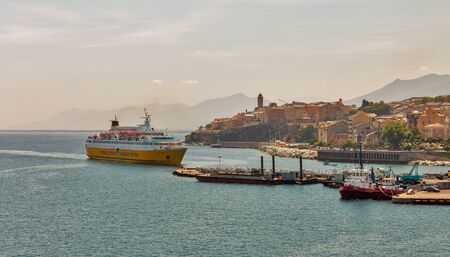 BASTIA, CORSICA, FRANCE - JULY 23, 2019: Seaside view of cityscape with Corsica Victoria by Corsica Ferries Sardinia Ferries ship enters port. Bastia port is busiest French port on Mediterranean Sea.