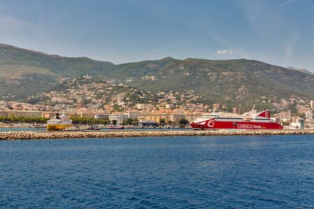 BASTIA, CORSICA, FRANCE - JULY 23, 2019: Cityscape with passenger port and moored ferry ships. Bastia port is the busiest French Mediterranean port. 에디토리얼