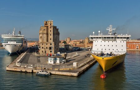 LIVORNO, ITALY - JULY 23, 2019: Seven Seas Voyager luxury cruise ship for Regent Cruises and Mega Express Three ferry ship for Corsica Ferries - Sardinia Ferries moored in port. 스톡 콘텐츠 - 133523782