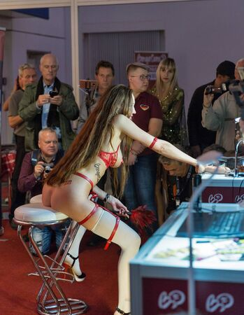 BERLIN, GERMANY - OCTOBER 17, 2019: Woman actress works at Bonga Cams online porno video live cams booth during 23th Venus and lifestyle trade fair in Messe exhibition hall.