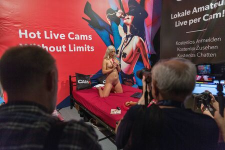 BERLIN, GERMANY - OCTOBER 17, 2019: People visit Hot Live Cams online amateur booth at Venus trade fair with trends and innovations from the and lifestyle in Messe exhibition hall.