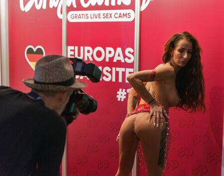 BERLIN, GERMANY - OCTOBER 17, 2019: Photographer and actress at Bonga Cams online porno video live cams booth during 23th Venus and lifestyle trade fair in Messe exhibition hall.