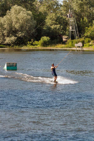 KYIV, UKRAINE - JUNE 05, 2015: Young man wakesurfing at cables wake park in sports and entertainment complex X-Park, Friendship of Nations Park, Yuryevskaya bay, Desenka river .