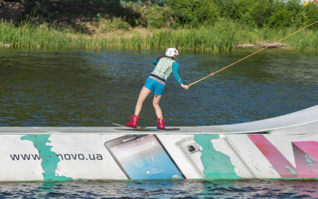 KYIV, UKRAINE - JUNE 05, 2015: Young woman wakesurfing at cables wake park in sports and entertainment complex X-Park, Friendship of Nations Park, Yuryevskaya bay, Desenka river .