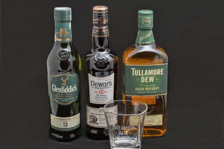 KYIV, UKRAINE - AUGUST 17, 2019: Bottles of Glenfiddich, Dewars and Tullamore DEW Scotch and Irish single malt and blended whisky against black background. Éditoriale