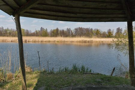 Quiet Ros riverbank in early spring with wooden gazebo, Ukraine