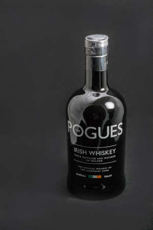 KIEV, UKRAINE - MAY 15, 2019: The Pogues blended Irish Whiskey triple distilled and matured bottle closeup against black background. It is the official whiskey of legendary band The Pogues. Banque d'images - 148560335