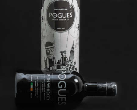 KIEV, UKRAINE - MAY 15, 2019: The Pogues blended Irish Whiskey triple distilled and matured bottle and box closeup against black background. It is the official whiskey of legendary band The Pogues. Banque d'images - 149032788