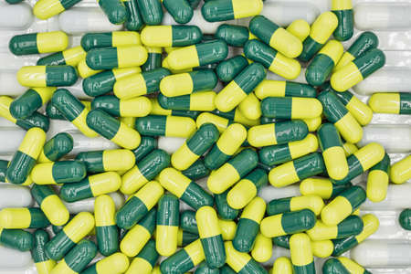 Medical capsules yellow green and blisters closeup background full frame