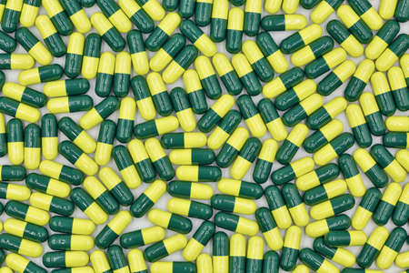 Medical capsules yellow green closeup background full frame