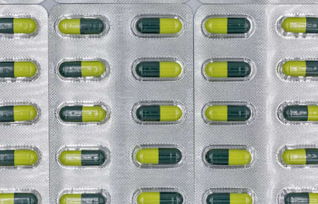 Medical capsules yellow green in white blisters closeup background full frame