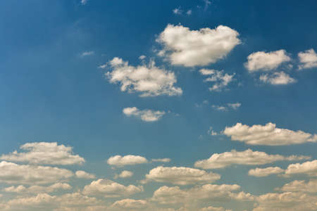 Cloudscape with white clouds against clear and blue sky