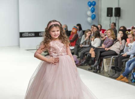 KYIV, UKRAINE - FEBRUARY 09, 2018: Fashion young little girl beautiful model at Kyiv Fashion 2018 in KyivExpoPlaza exhibition center. It is the main b2b event of Ukrainian fashion industry.