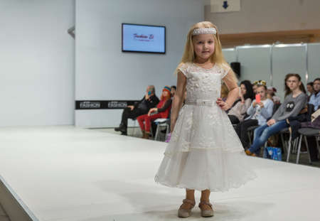 KYIV, UKRAINE - FEBRUARY 09, 2018: Fashion young little girl beautiful model at Kyiv Fashion 2018 in KyivExpoPlaza exhibition center. It is the main b2b event of Ukrainian fashion industry.