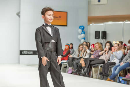 KYIV, UKRAINE - FEBRUARY 09, 2018: Fashion young little boy beautiful model at Kyiv Fashion 2018 in KyivExpoPlaza exhibition center. It is the main b2b event of Ukrainian fashion industry.