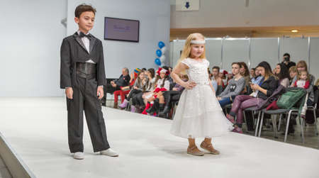 KYIV, UKRAINE - FEBRUARY 09, 2018: Fashion young little boy and girl beautiful models at Kyiv Fashion 2018 in KyivExpoPlaza exhibition center. It is the main b2b event of Ukrainian fashion industry. Éditoriale