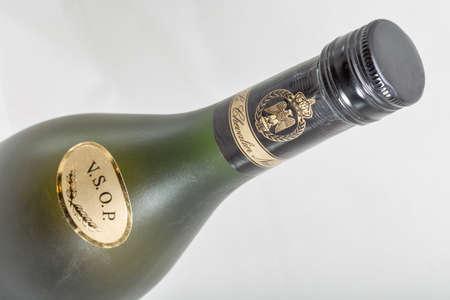 KIEV, UKRAINE - FEBRUARY 17, 2019: French pure grape V.S.O.P. brandy Napoleon old bottle neck with label closeup against white background.