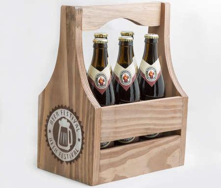 KYIV, UKRAINE - OCTOBER 27, 2019: German Franziskaner dark Weissbier bottles closeup against white background in wooden basket. Wheat dark and white beer brewed in Munich, Germany since 1397.