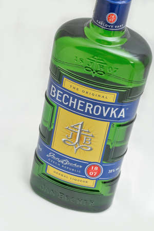 KYIV, UKRAINE - DECEMBER 31, 2019: Czech herbal bitter Becherovka bottle closeup against white background. It is produced in Karlovy Vary, Czech Republic by the Jan Becher company. Éditoriale