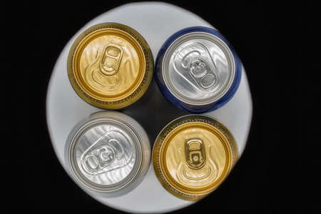 different closed beer drinking cans closeup view from above through circle hole in black