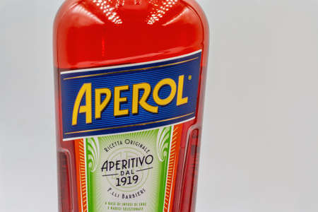 KYIV, UKRAINE - DECEMBER 16, 2020: Studio shoot of Aperol Aperitivo Liqueur bottle label closeup against white. Famous Italian aperitif produced by DCM Spa, Italy.
