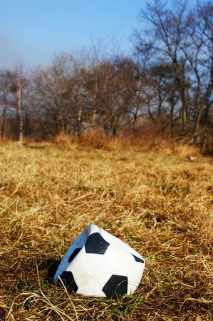 Deflated soccer ball on the dry grass Stock Photo