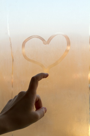Sweaty drawing hearts on the window Stock Photo
