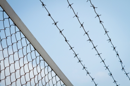perimeter: Barbed wire and metal mesh against the sky Stock Photo