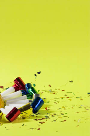Blowers and confetti over green background