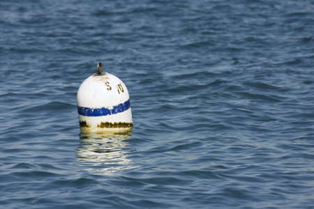 Lonely white buoy floating in the lake