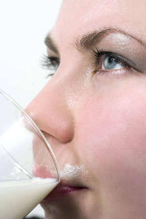 Girl drinking milk, close up, over white