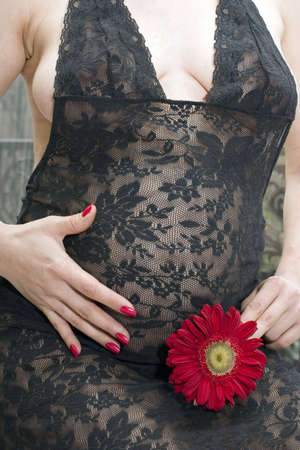 Close up of a pregnant woman's belly with a flower