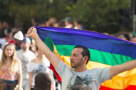 bandera gay: SAO PAULO, BRASIL - 7 de junio de 2015: Un gay no identificado con la bandera del arco iris, lesbiana celebrando, gay, bisexual, transgénero y la cultura en el 19o Desfile del Orgullo Gay de Sao Paulo
