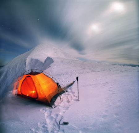 The tent is set on a hillside in winter the most beautiful and the big mountain in the Carpathians-Goverla.  Stock Photo