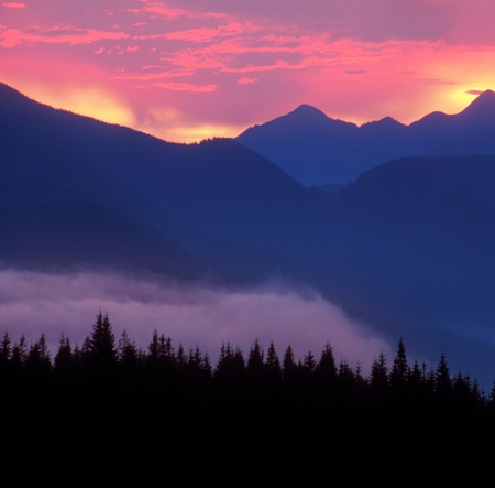 A beautiful sunset in the sunny foothills of the Alps affects the viewers imagination, dense forests on the slopes conceal the traces of civilization photo