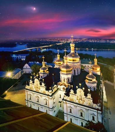 The moon on the crimson dawn sky hangs over the ancient temples of the main Christian shrines of Ukraine. Kiev-Pechersk Lavra, an Orthodox Christian monastery has a thousand-year history 版權商用圖片