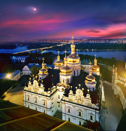 The moon on the crimson dawn sky hangs over the ancient temples of the main Christian shrines of Ukraine. photo