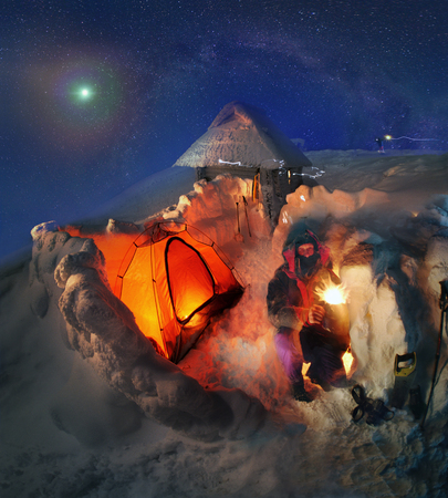 Ukrainian tourists celebrate New Year in extreme conditions on the glacier, the highest peak in the country- Goverla, Montenegrin ridge, 2061 meters, building a protective snow wall tent. Moonrise complete with a clear sky photo