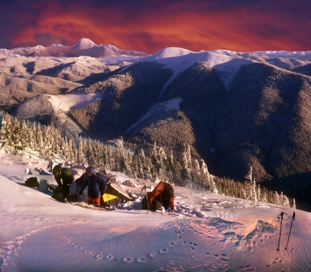 In anticipation of the storm troop of tourists preparing for the harsh spending the night on a high mountain in the Carpathians. Strong wind and snow and catch up with them the next morning. Stock Photo - 24885584