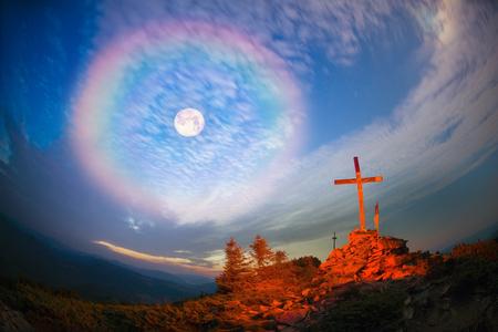 under fire: Cruz en el Monte Strymba madera elevado a la gloria de Dios, Jesucristo. luz de noche que enciende un fuego en un fondo de piedras vegetación montañas alpinas bajo las estrellas de la Vía Láctea