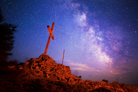 Cross on Mount Strymba wooden raised to the glory of God, Jesus Christ. Night light lighting a fire on a background of mountains alpine vegetation stones under the stars of the Milky Way Stock Photo
