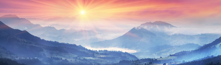 highlanders: sunrise, the suns rays illuminate the beautiful panorama of the Carpathian village against backdrop of scenic mountains, where the highlanders live Hutsul. Wild forests, fields pastures