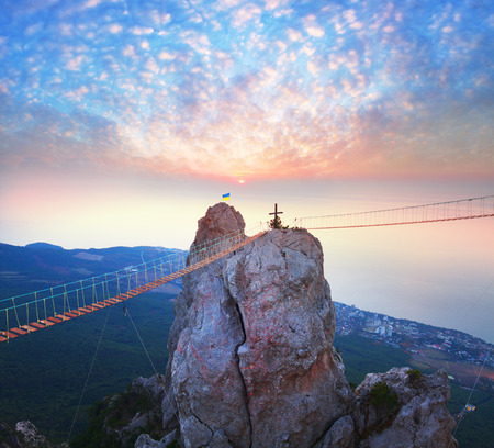 occupied: Rocks teeth above Yalta - celebrity Russia occupied Crimea. Ukrainians on the top of the cliff and cross Ukrainian climbers pulled the bridge for the development of extreme tourism.